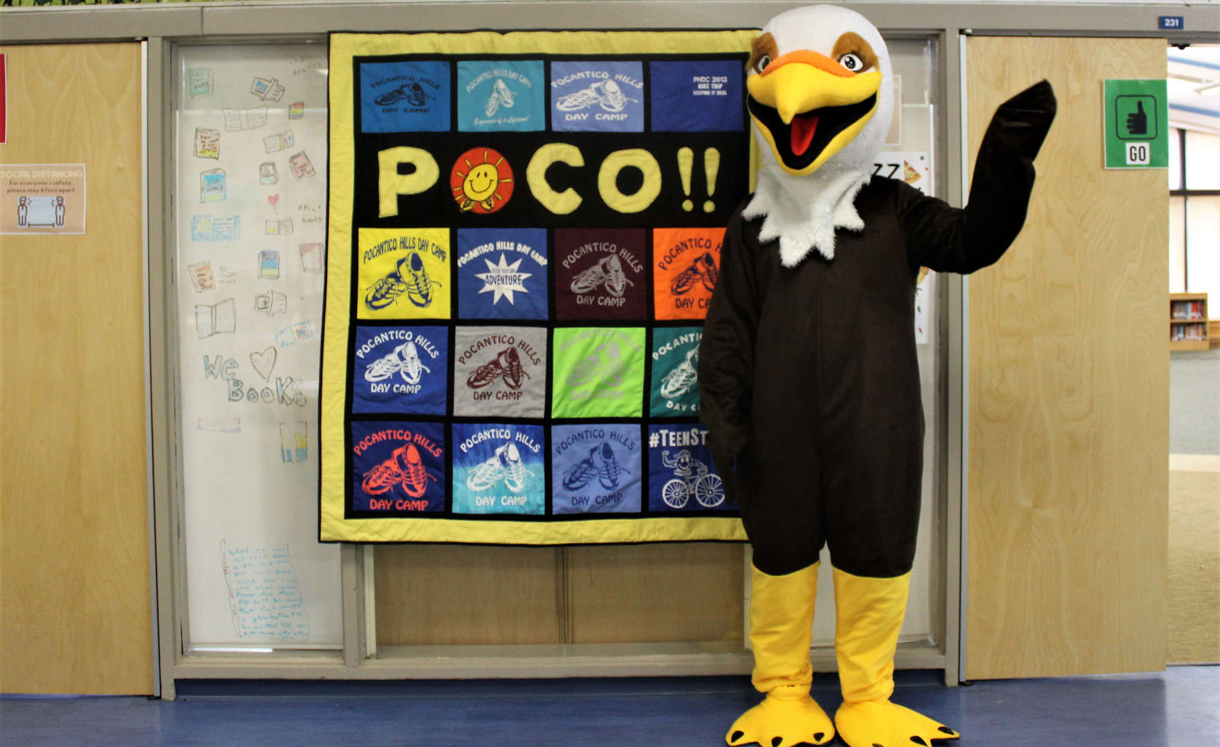 A person dressed as Skye, the camp's new hawk mascot, stands in front of a camp quilt.
