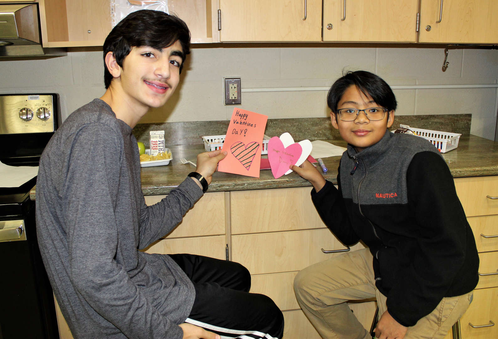 Two male students make cards for Valentine's Day.