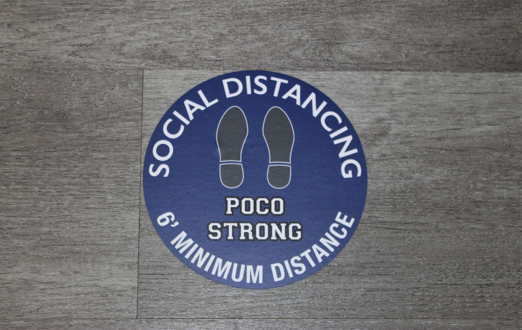Social distancing/Poco Strong stickers like this one are on floors throughout the school.
