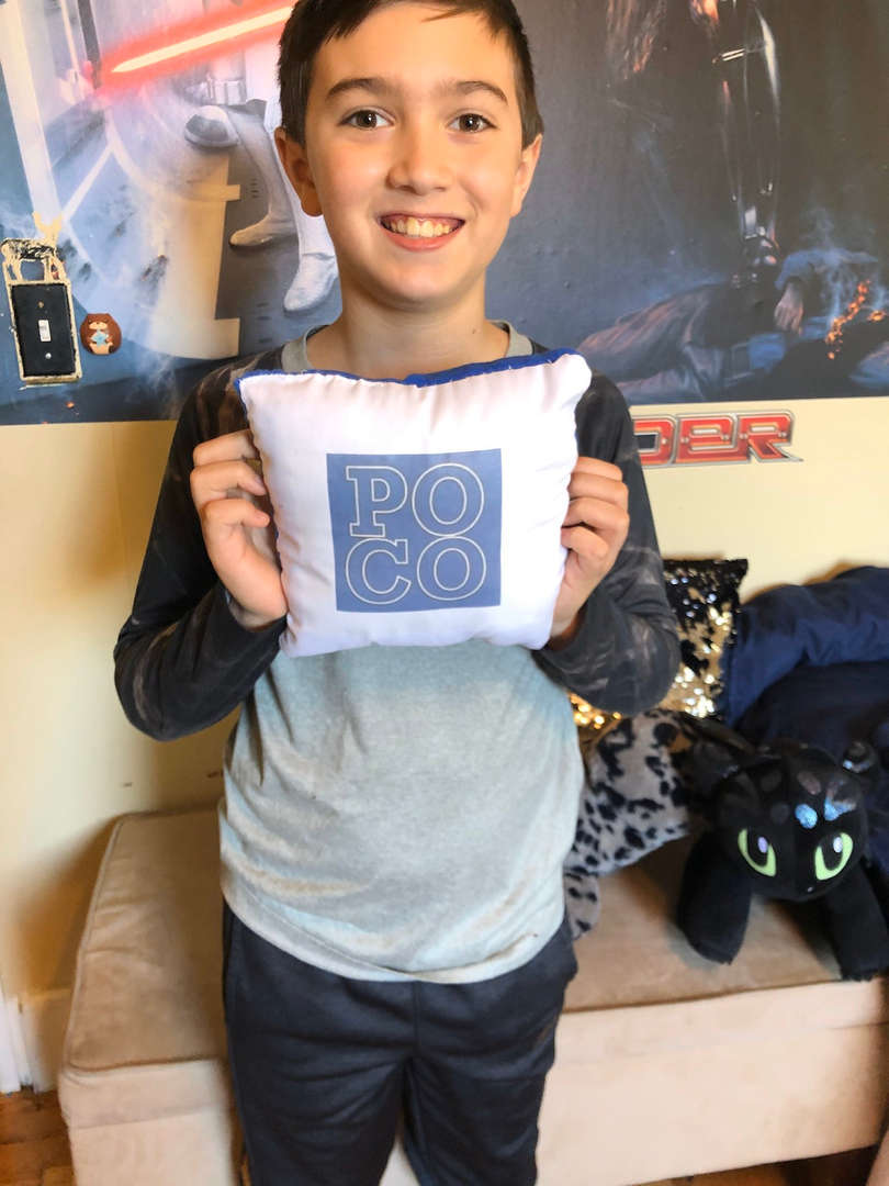 A boy holds up a Poco pillow that he made.