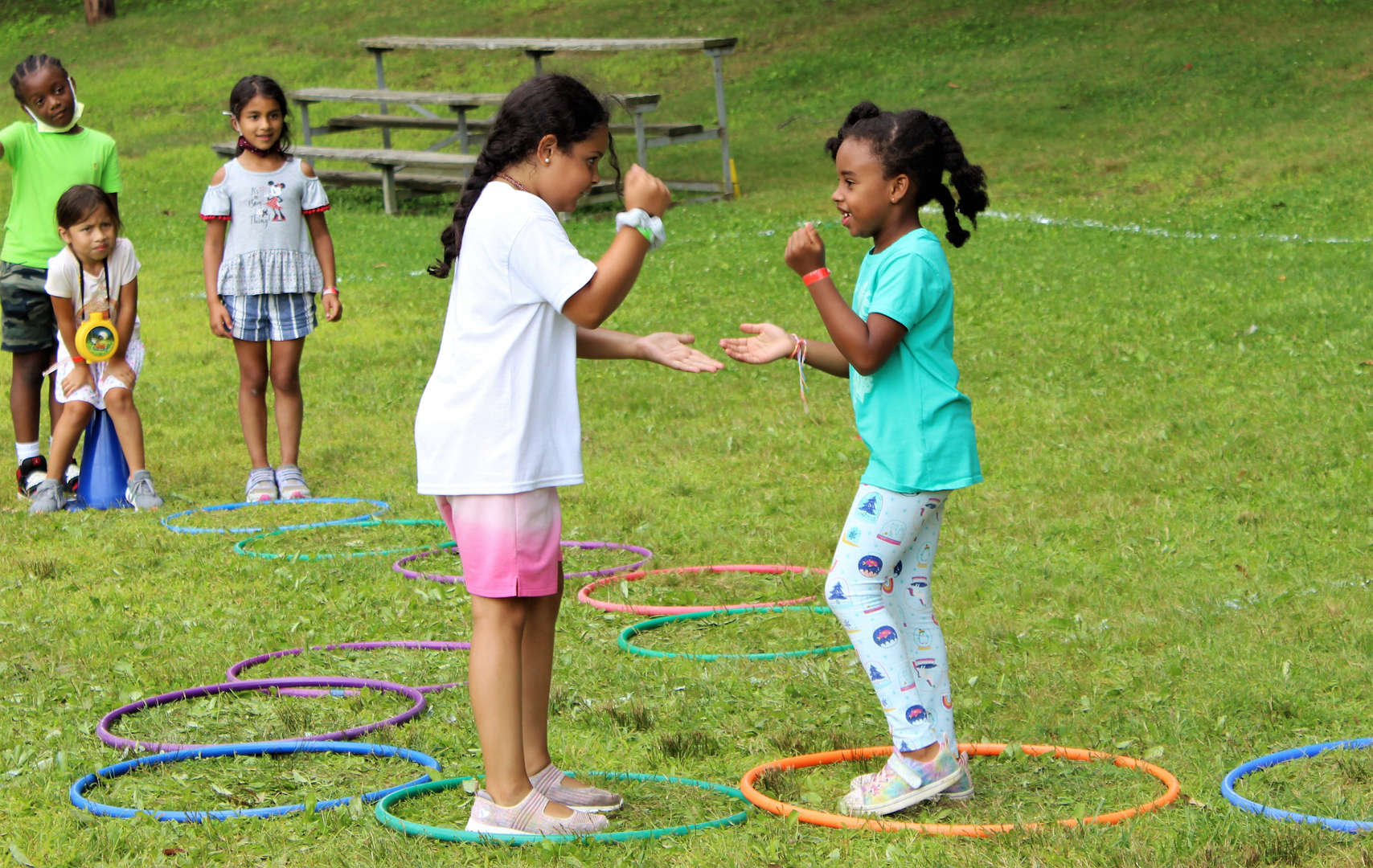 Two girls square off in a game that involved hula hoops, hopping and the game rock, paper, scissors.