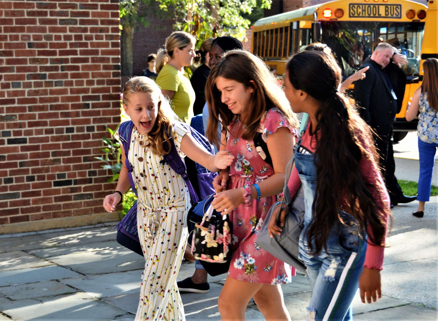 Three girls enter the school building on the first day back.