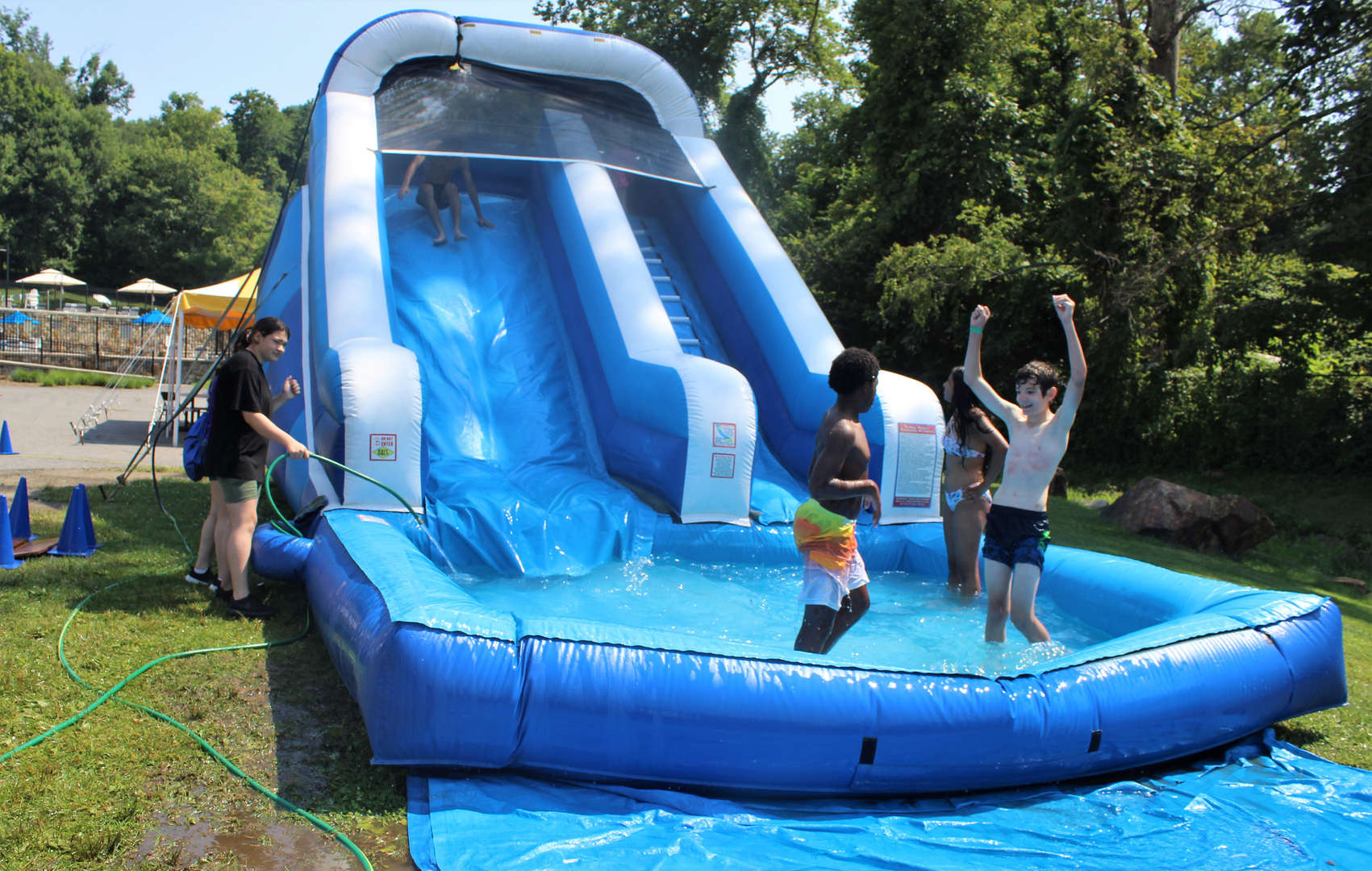 A boy pumps his arms up after sliding down the water slide.
