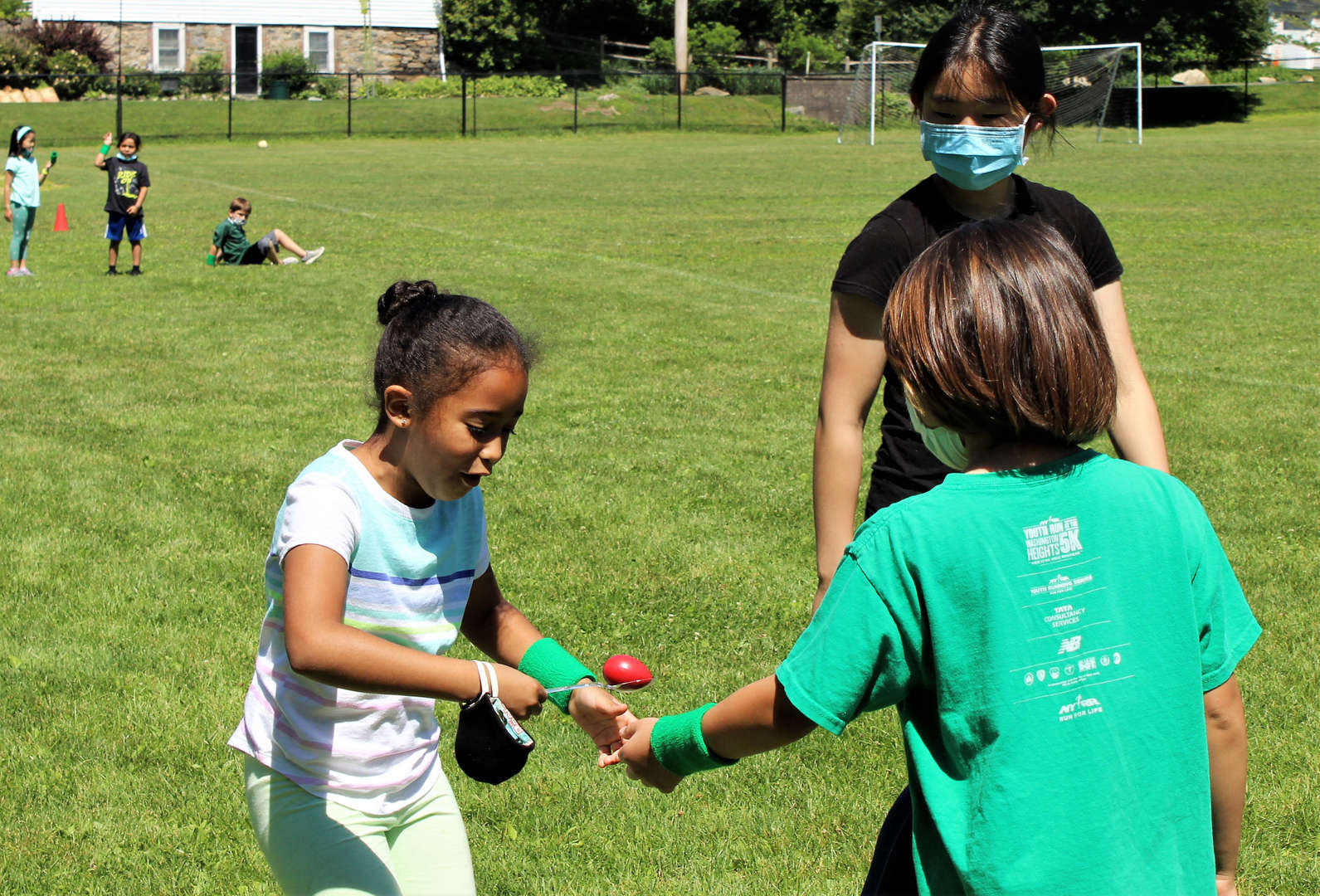 """One student passes off a spoon with an """"egg"""" to another during a relay."""