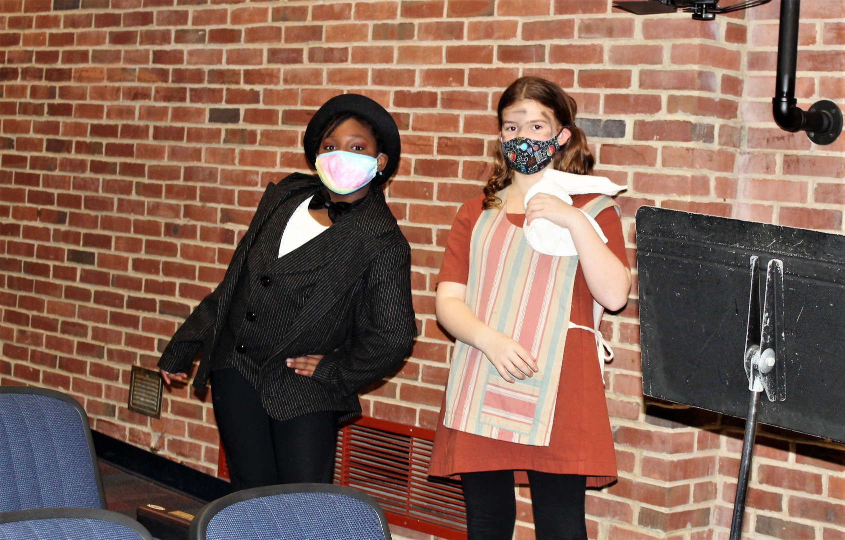 Two female students dressed for their parts as Daddy Warbucks and an orphan.