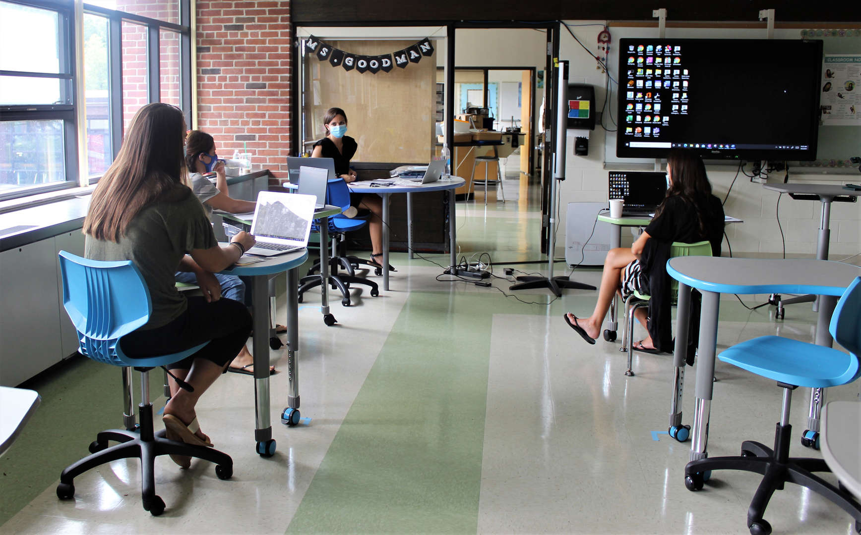 Four female teachers plan curriculum for the year in a classroom.