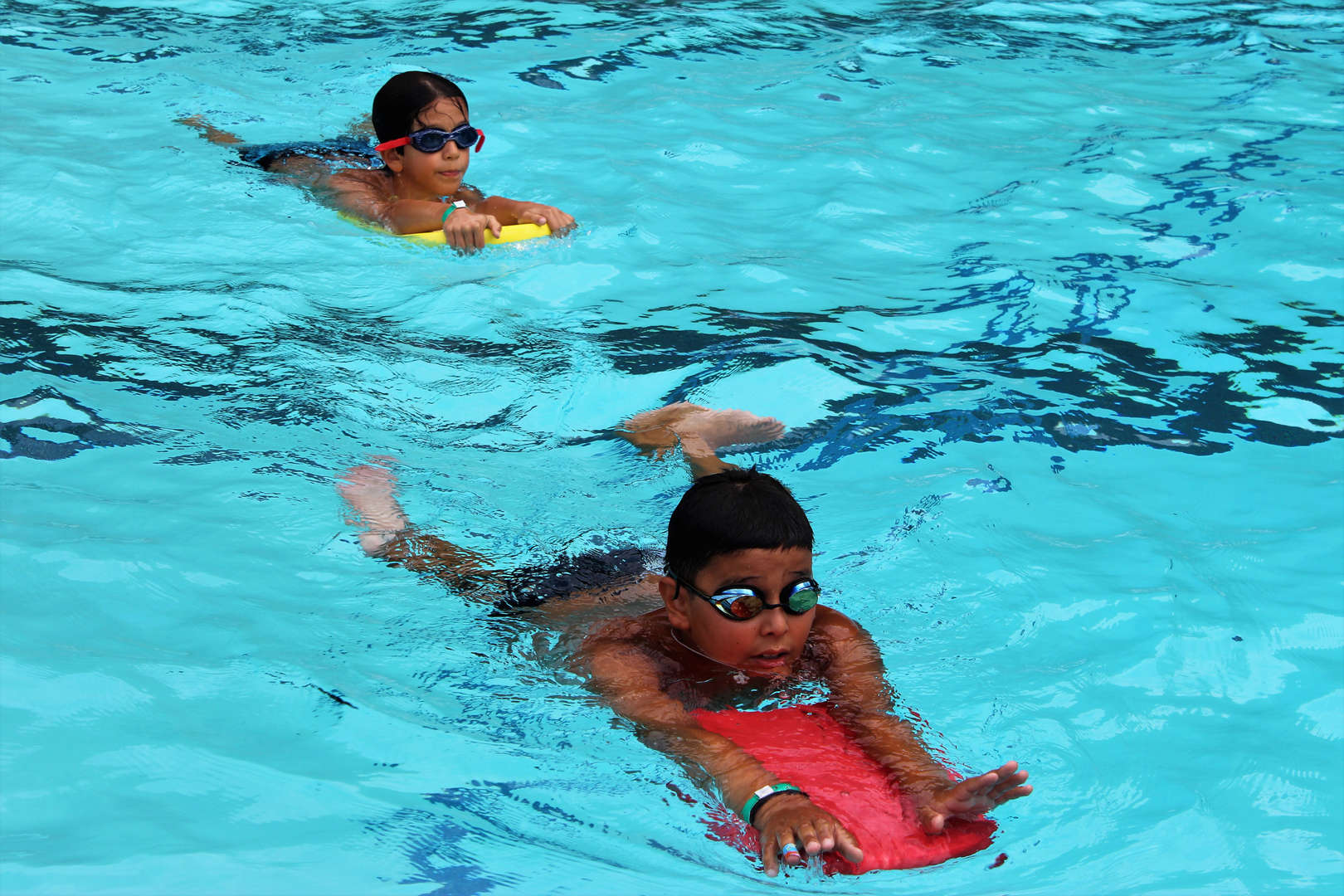 Two boys swimming at the school pool.