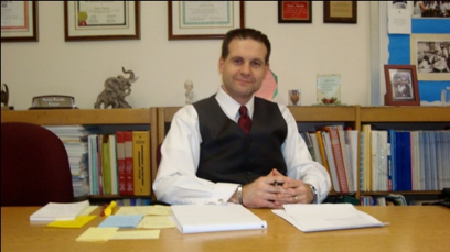 A picture of the school principal, Dimitres Pantelidis, in his office
