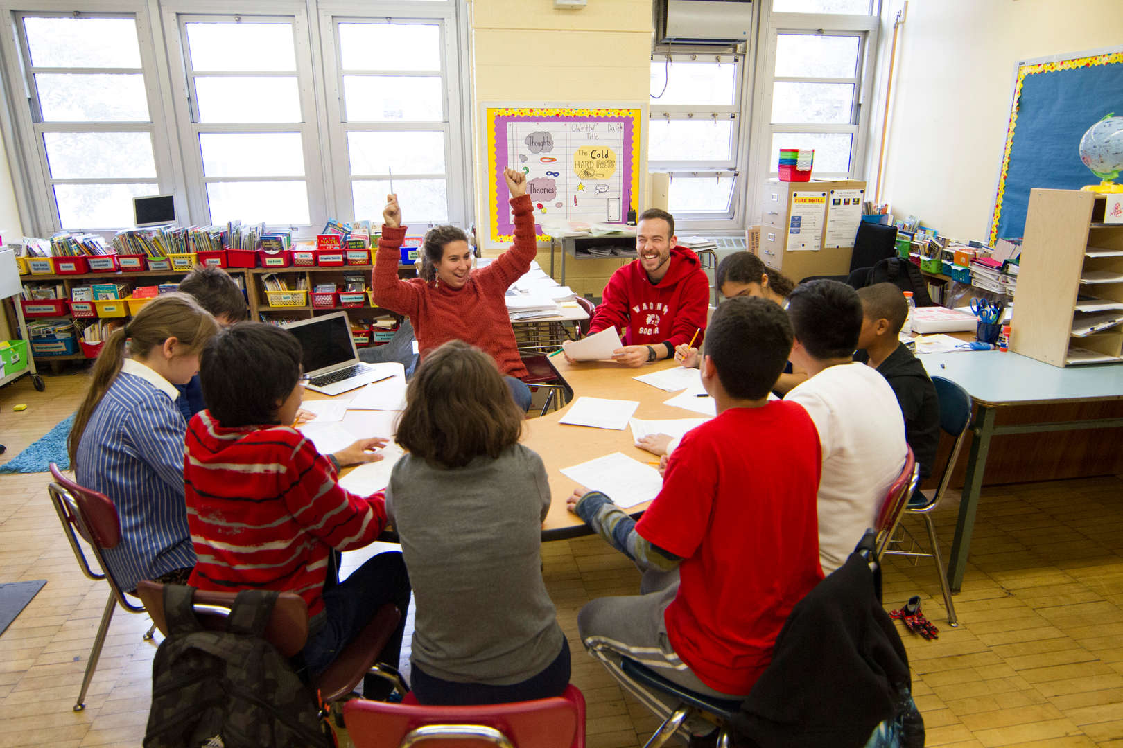 Students sit in circle with teachers for collaborative learning