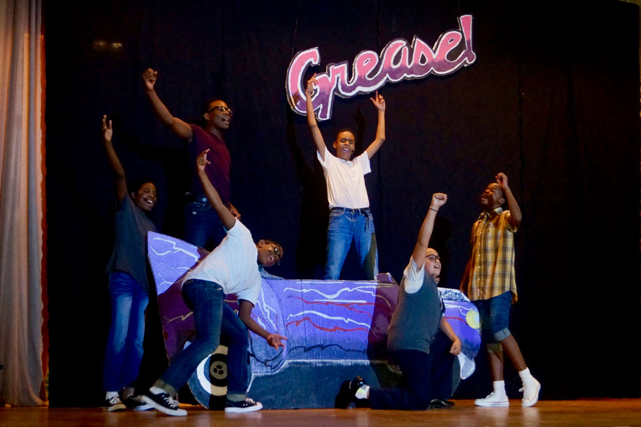 Character holding up Grease sign