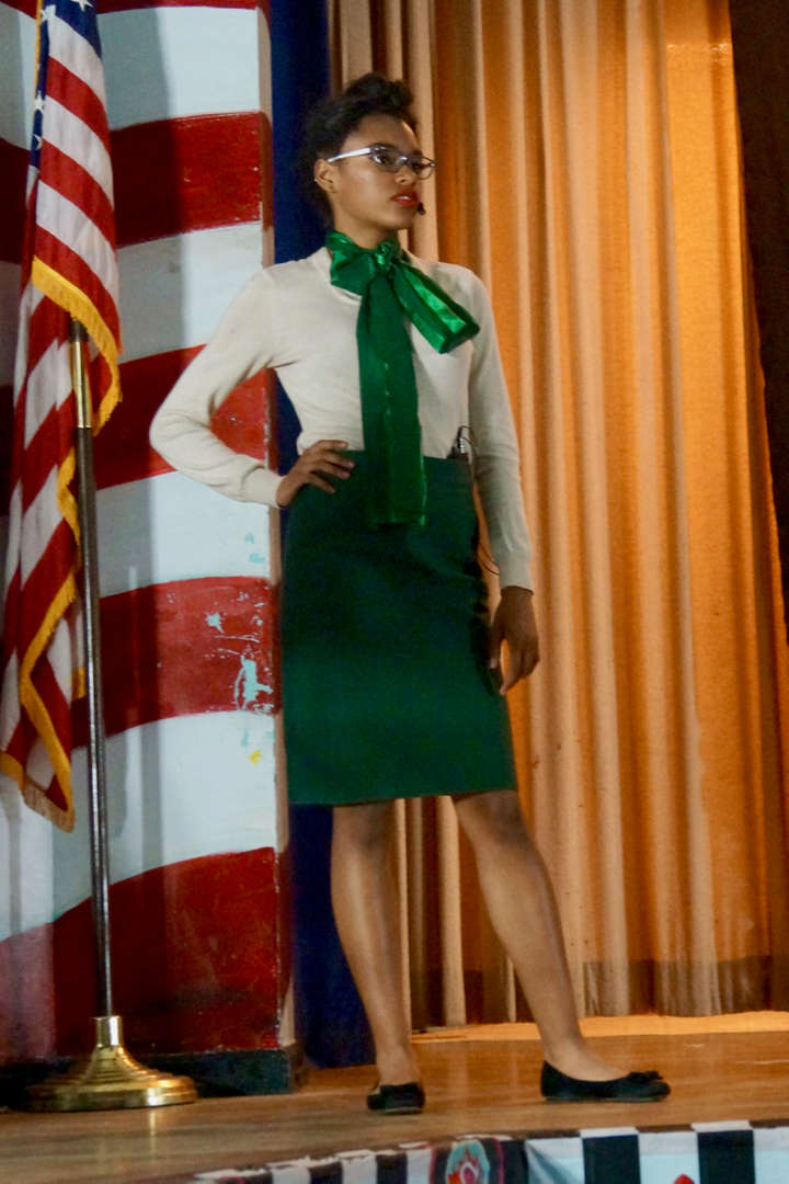 Actor in green pencil skirt standing with hand on hip