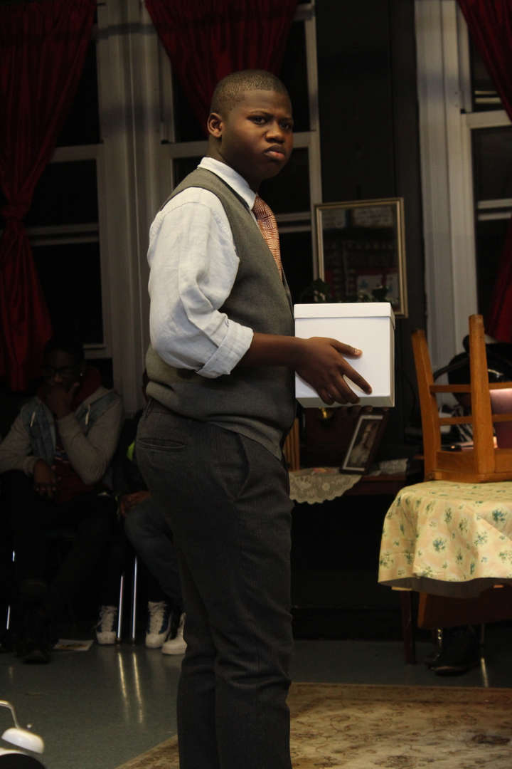 Actor wearing a waistcoat holds a white box