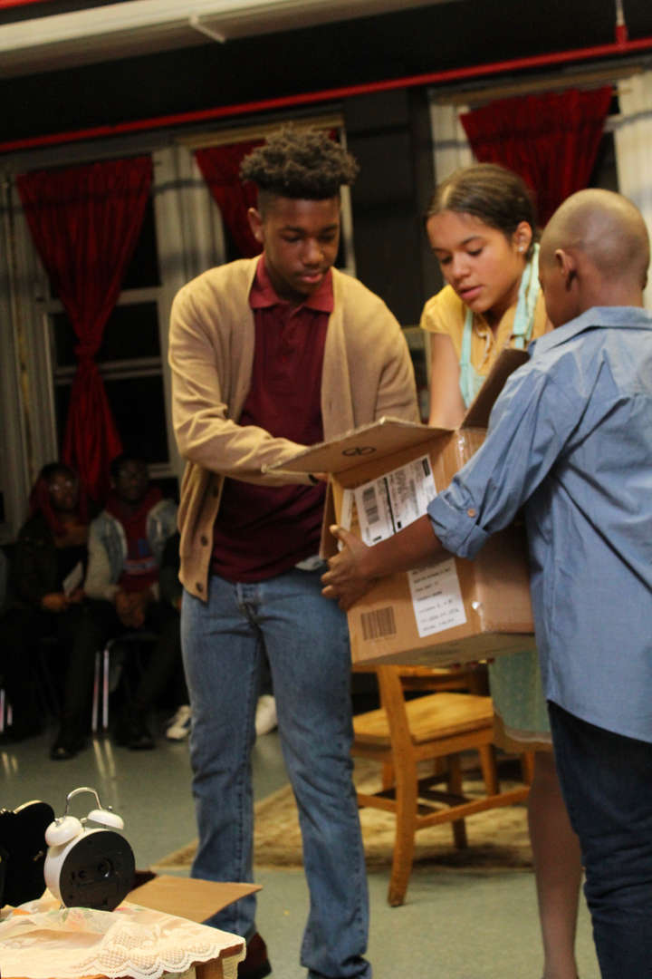 Two actors and a younger child take things out of a cardboard box