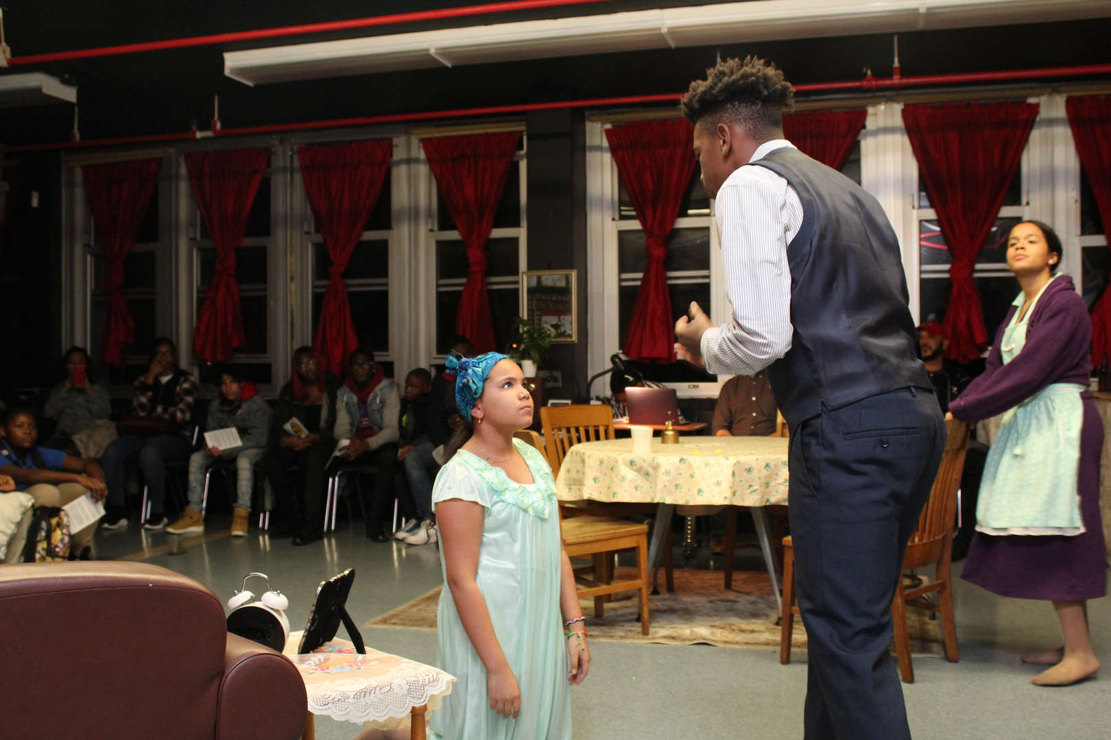 Actress in a blue dress on her knees in front of a formally dressed actor