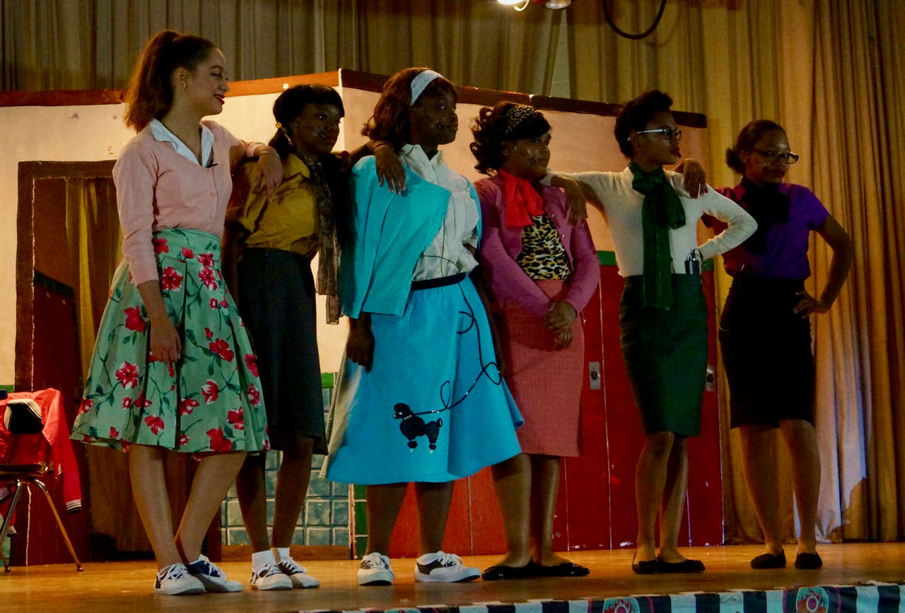 Student in bright blue outfit on stage with other actors