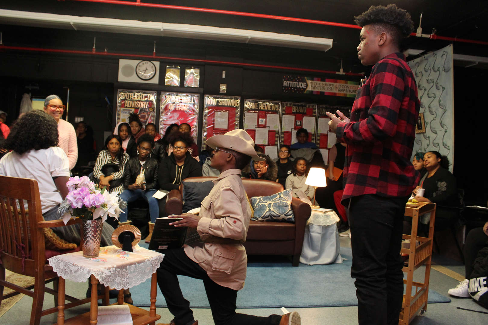 Three actors listen to as an actress dressed as an elderly woman speak