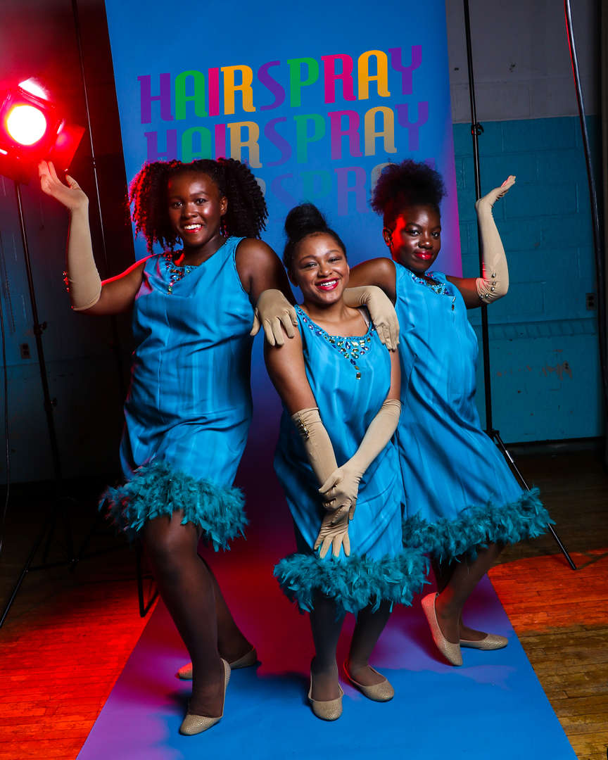 Three actors in blue dresses posing with one another