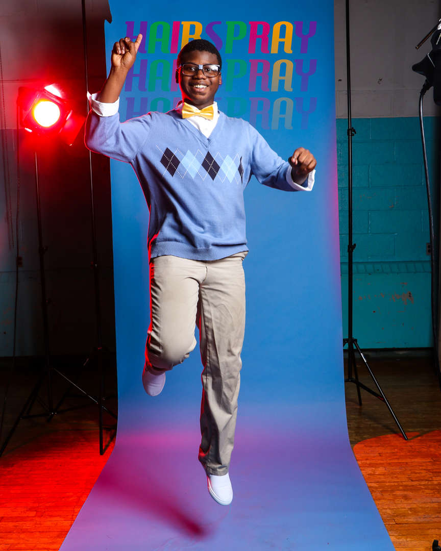 Student in light blue sweater jumping