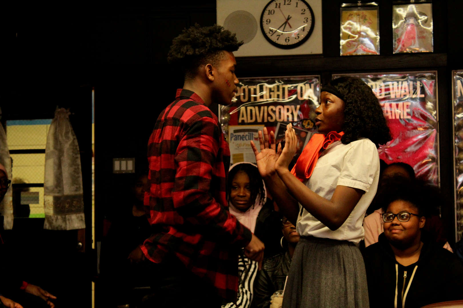 Actor dressed in a red flannel approaches an actress with her hands up