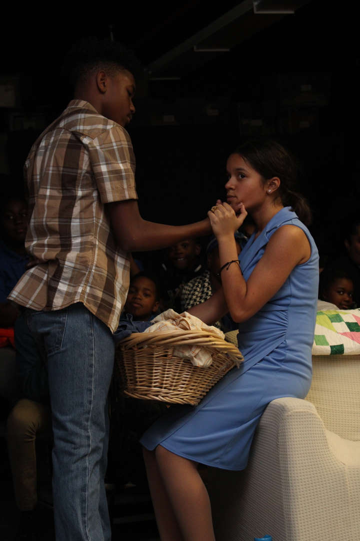 Actor caresses the face of an actress in a blue dress holding a laundry basket