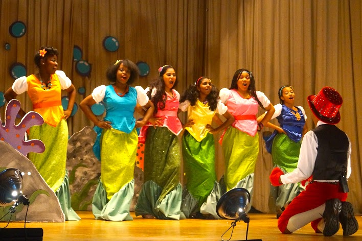 Students dressed as mermaids singing