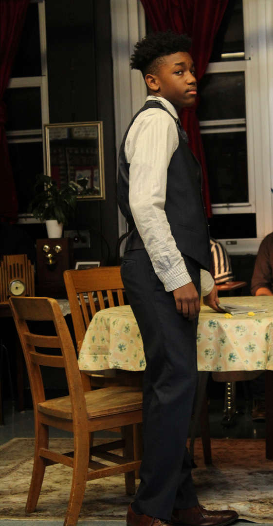 Actor dressed in a waistcoat standing in front of a dining table