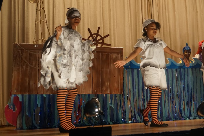 Students dancing dressed in white dresses and striped stockings