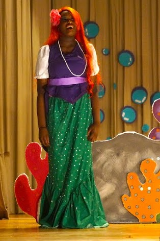 Actress dressed as the Little Mermaid singing