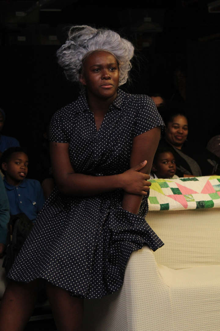 Actress in a polka dot dress and gray wig