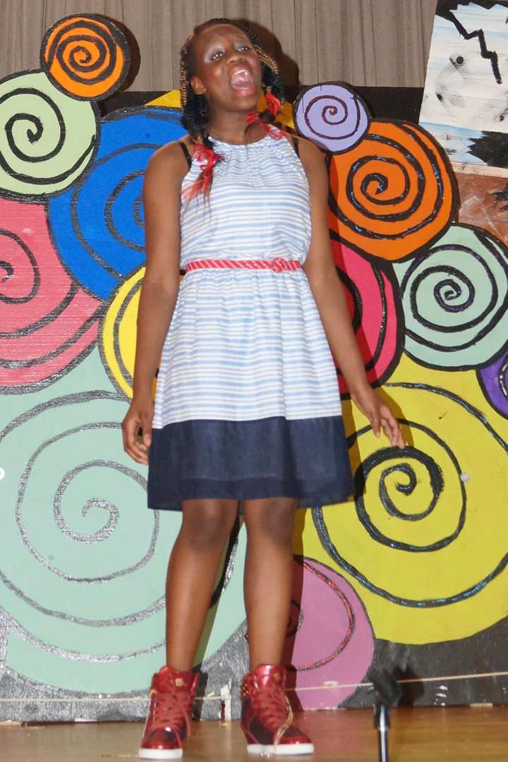 Student on stage in front of colorful swirls