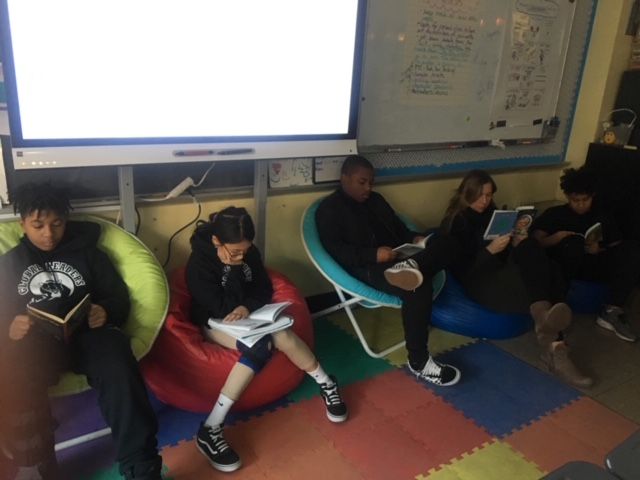 Students sit on floor in front of the classroom.