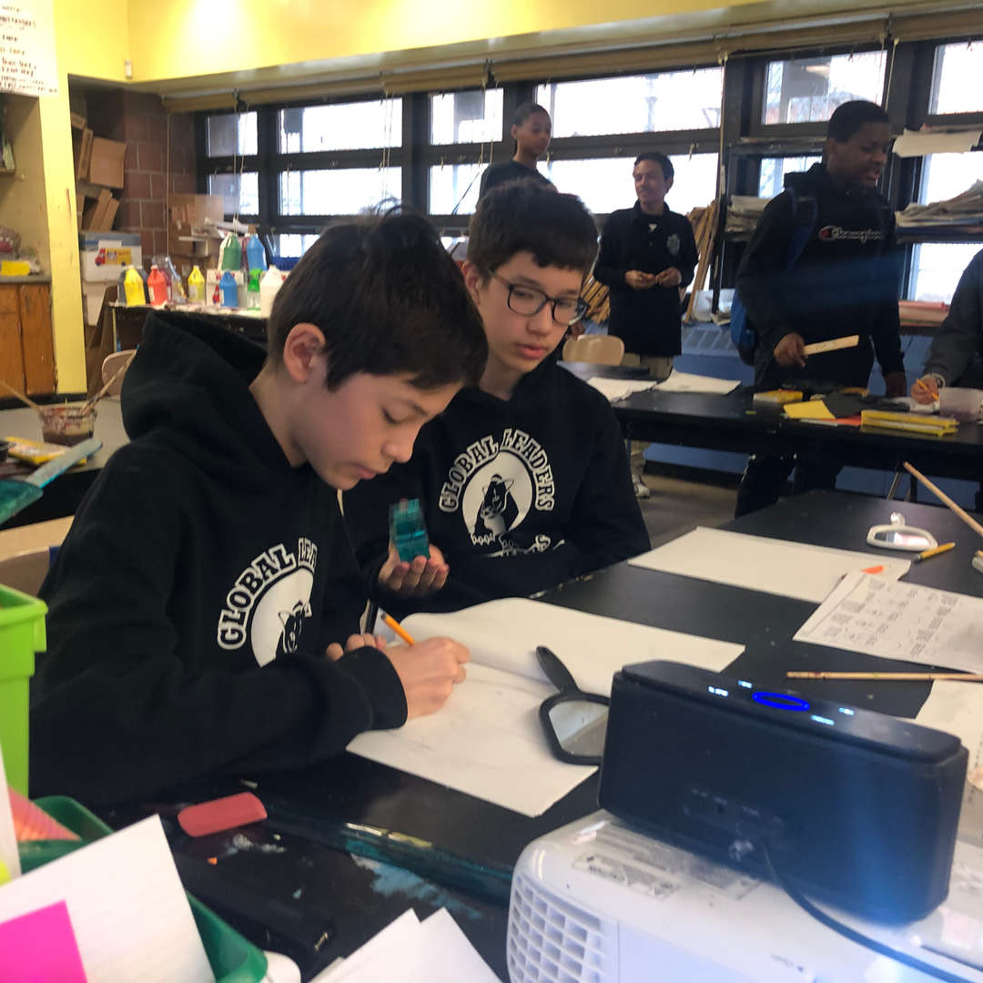 Students with school sweatshirts on writing on a desk.