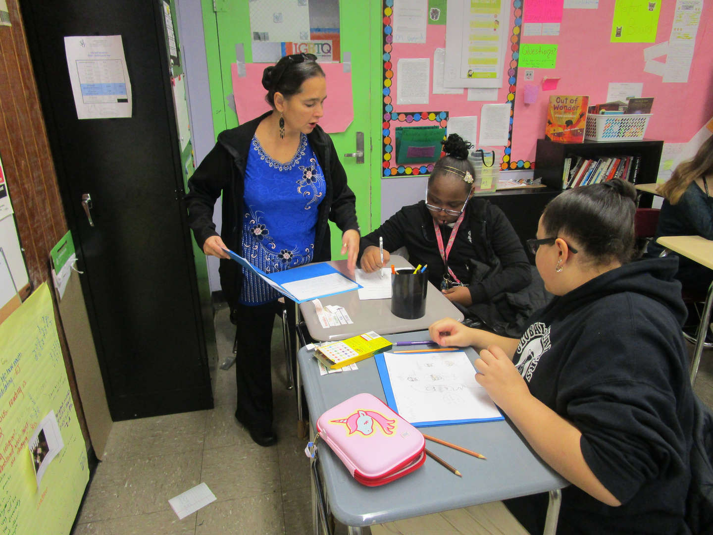 Teacher assists two students.