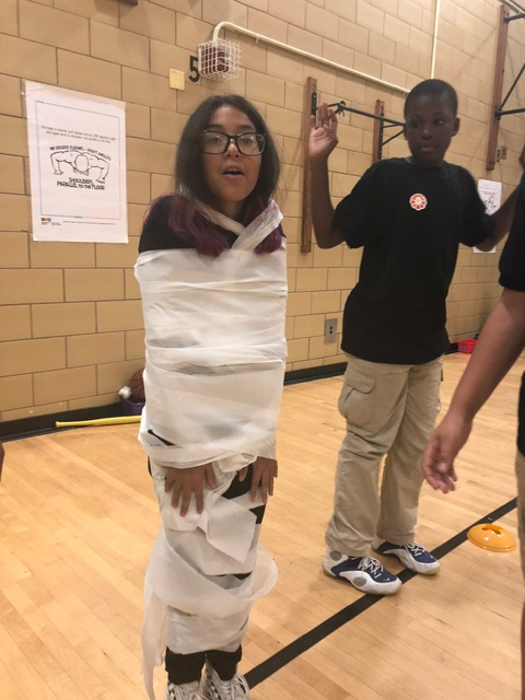 Student wrapped in toilet tissue smiling.