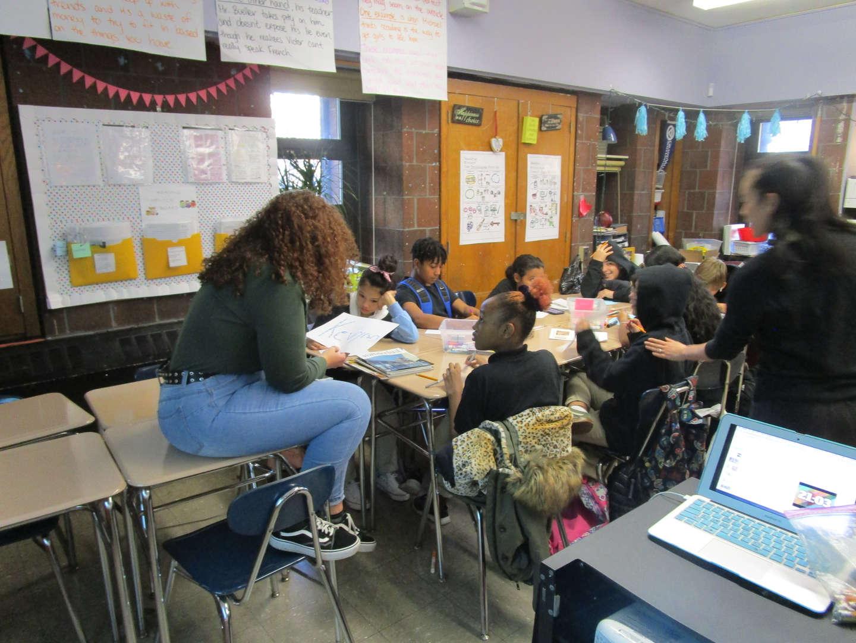 Teacher sits on desk while teaching.