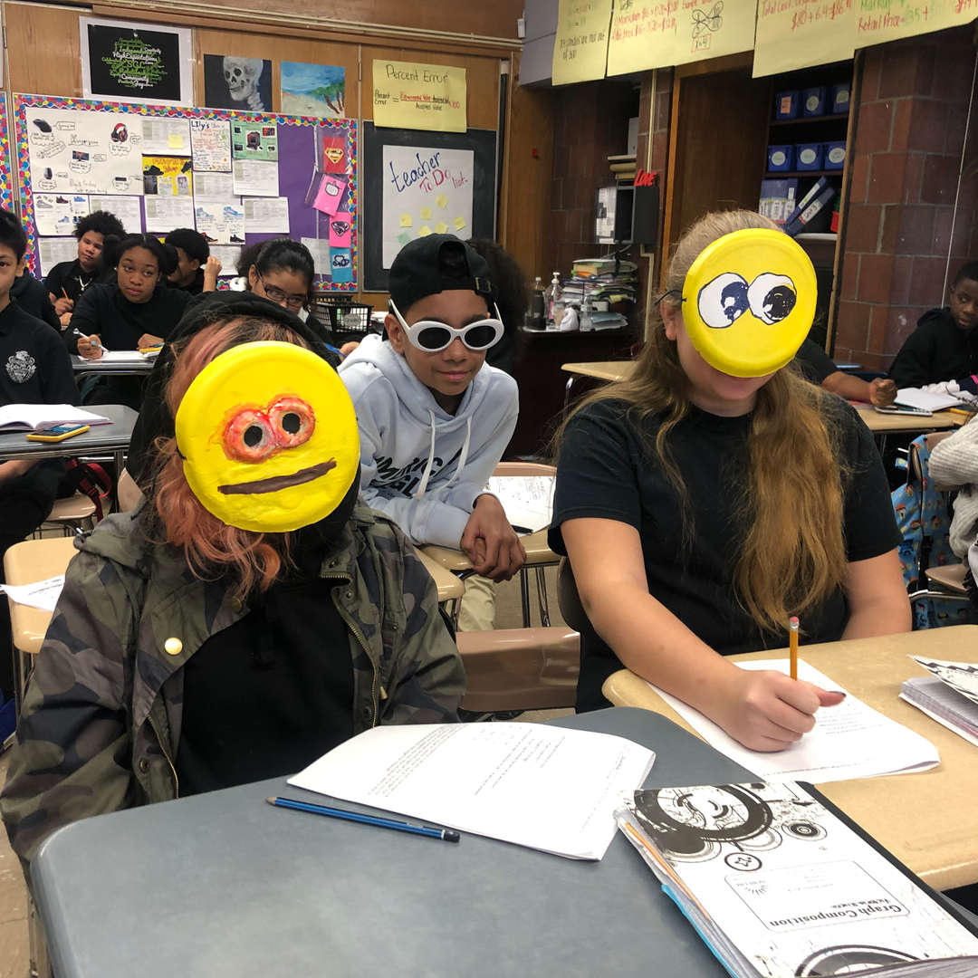 Students with made-up emoji faces on.