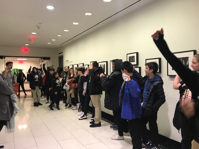 Students in a museum lined against the wall.