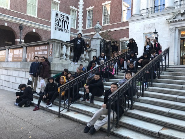 Students outside sitting on steps.