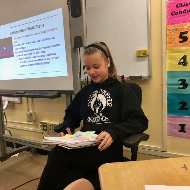 Student is sitting down and reading a book.