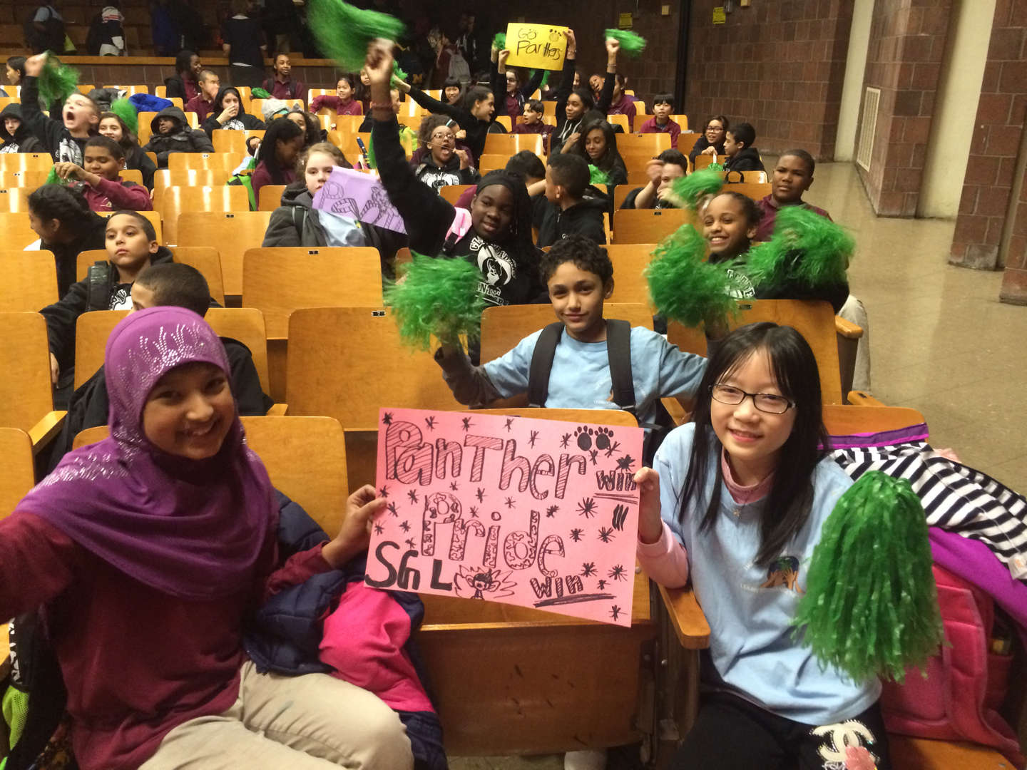 Students in auditorium displaying school pride.