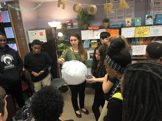 Students stand in a circle talking.