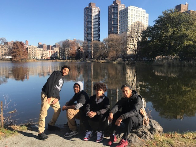 Students on a field trip posing in front of a lake.