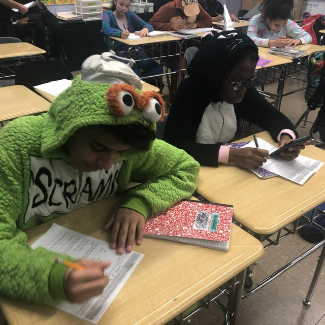 Student with a green costume on is doing classwork on a desk.