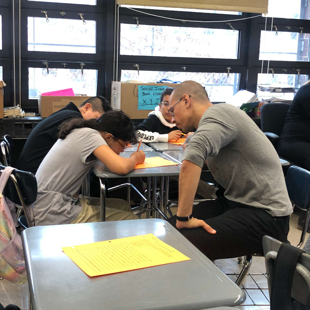 Teacher sits and assists a student with head down.
