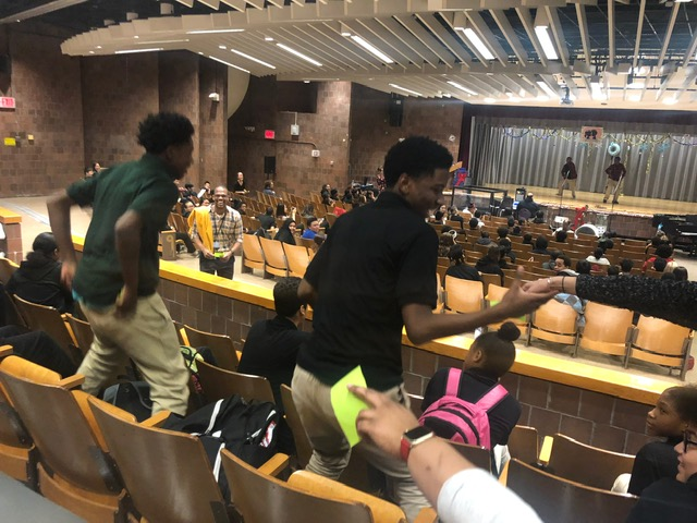 Students moving out of an aisle in the school auditorium.