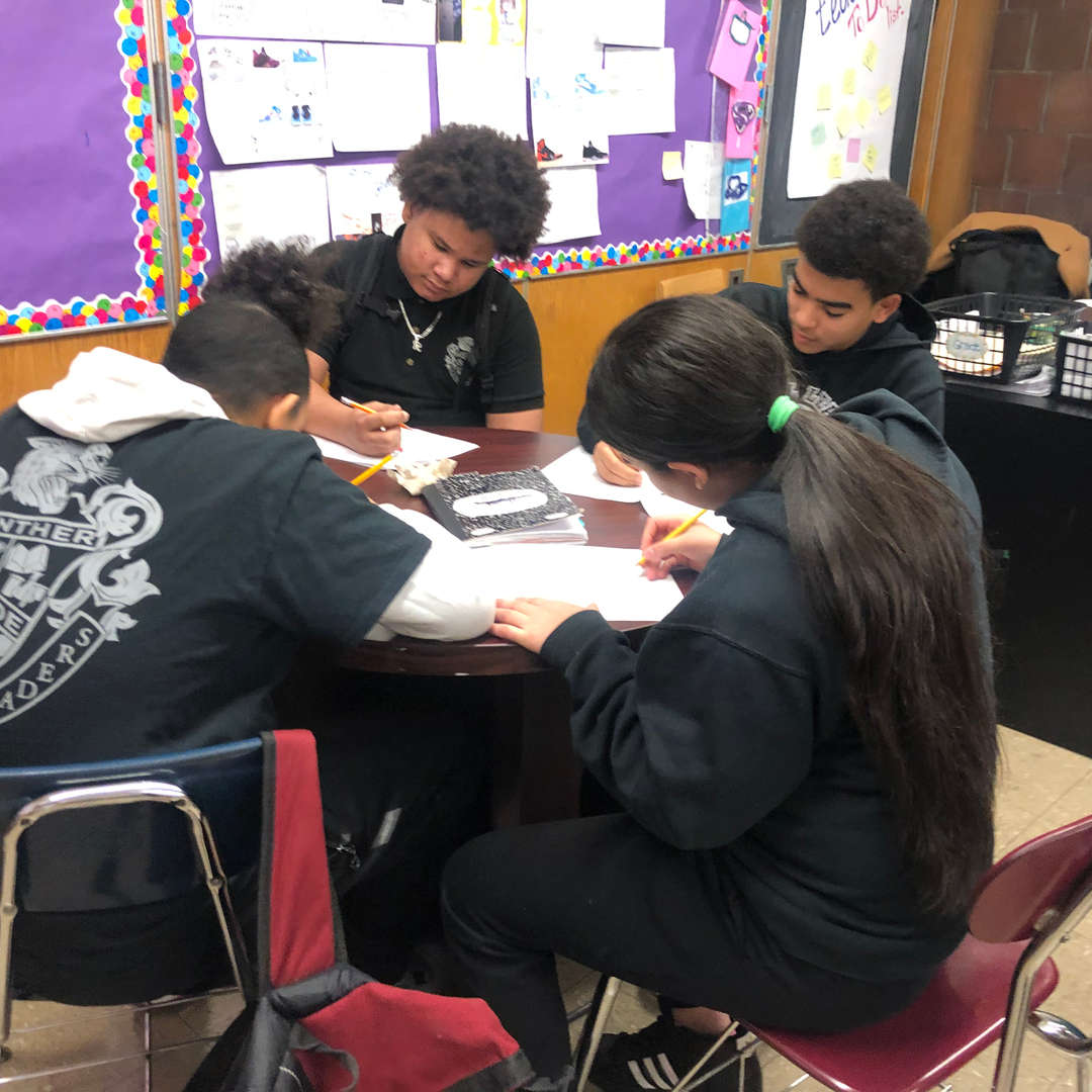 Students in a group sitting and working.
