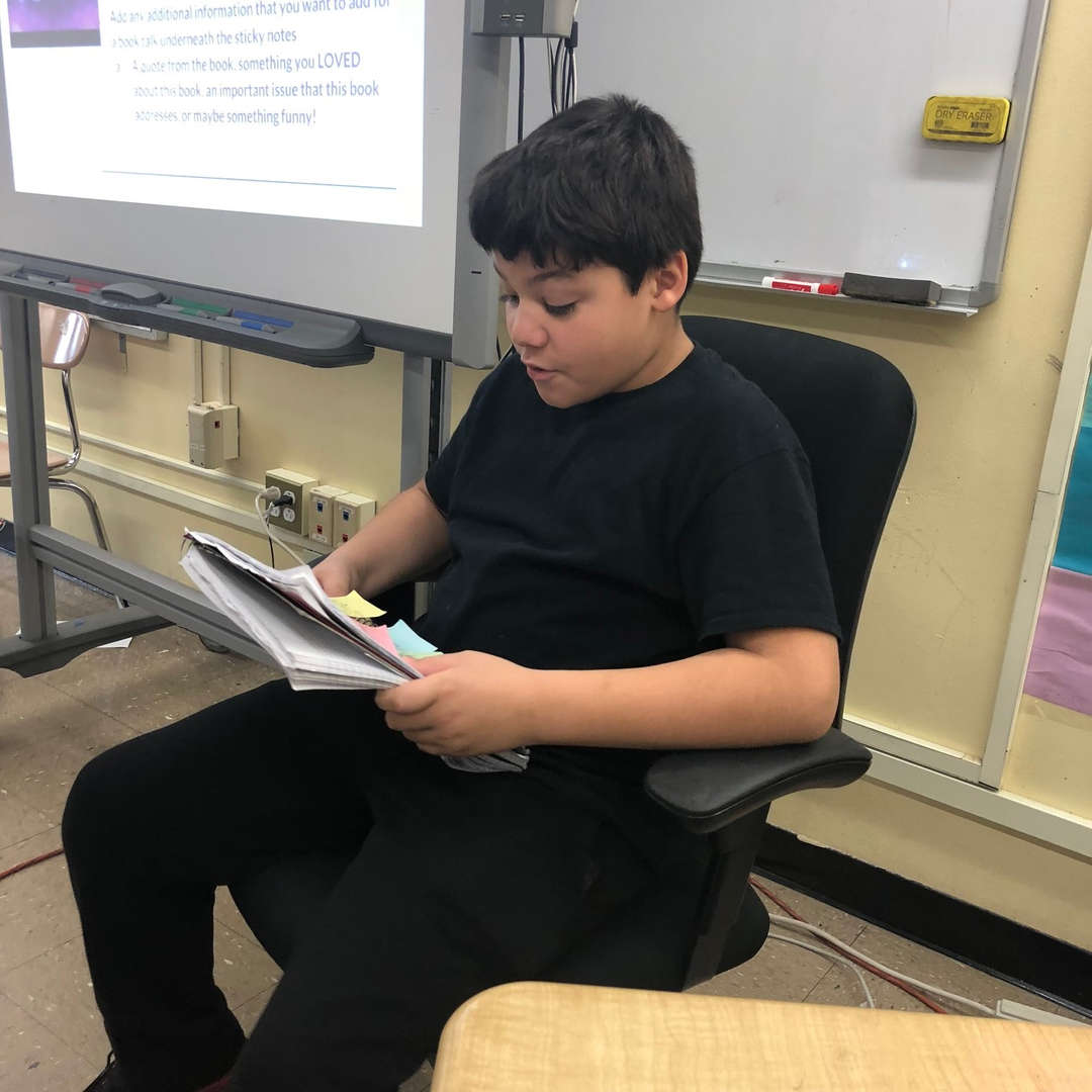 Student is sitting in chair reading a book.