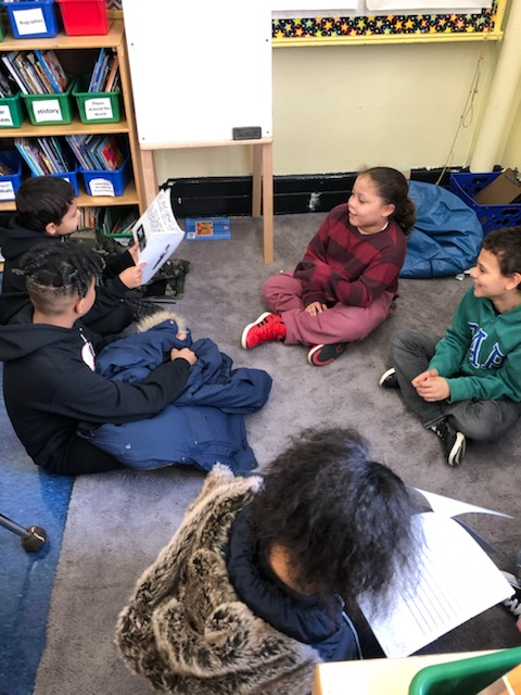 Students sit on the floor and talk.