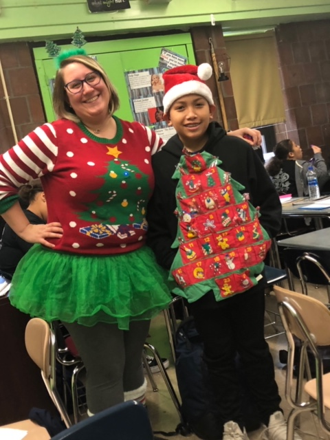 Two teachers pose in Christmas outfits.