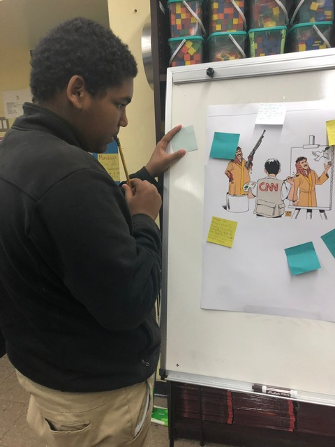 Student looking at another student's artwork on the whiteboard.